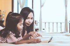 Мать и дочь счастливой семьи азиатская прочитали книгу совместно Стоковое Фото