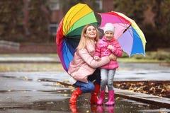 Мать и дочь с зонтиками принимая прогулку осени в городе стоковые фотографии rf