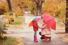 Мать и дочь с зонтиками принимая прогулку стоковые фото