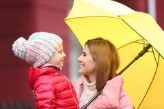 Мать и дочь с зонтиком в городе на день осени стоковая фотография rf