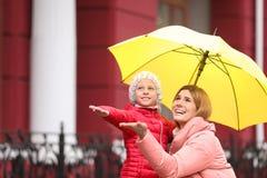Мать и дочь с зонтиком в городе стоковое фото rf