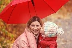 Мать и дочь с зонтиком в парке осени стоковое фото