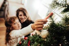 Мать и дочь украшая рождественскую елку Стоковая Фотография RF