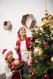 Мать и дочь украшая рождественскую елку Стоковые Фото