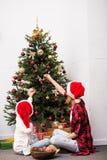 Мать и дочь украшая рождественскую елку Стоковые Изображения RF