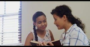 Мать и дочь читая книгу совместно 4K 4k акции видеоматериалы