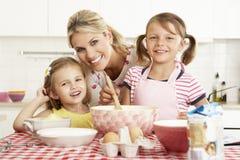 Мать и 2 девушки печь в кухне Стоковая Фотография