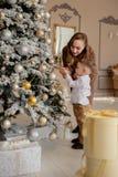 Мать и его маленький сын украшая рождественскую елку с игрушками и гирляндами стоковые изображения