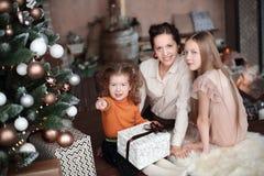 Мать и ее дочери раскрывая подарочную коробку около рождественской елки стоковые фото