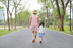 Мать и ее дочь идя на дорогу и держа руки в на открытом воздухе саде природы E стоковое фото rf
