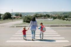Мать и ее дети пересекая дорогу Стоковые Фото
