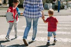 Мать и ее дети пересекая дорогу Стоковые Изображения RF