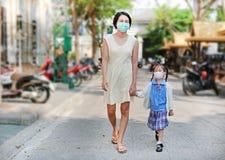 Мать и ее идти дочери идут обучить с носить маску защиты против премьер-министра 2 загрязнение воздуха 5 в городе Бангкока r стоковое изображение