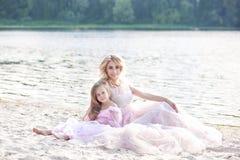 Мать и ее маленькая девочка наслаждаясь видом на озеро и ослабляя на пляже на солнечный день в красивых платьях Образ жизни семьи стоковая фотография