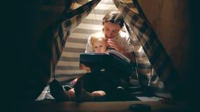 Мать и ее маленький младенец прочитали книгу совместно в уютном освещенном teepee в вечере сток-видео