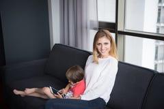 Мать и ее милая маленькая дочь используют таблетку Стоковое фото RF