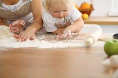 Мать и ее милые руки дочери подготавливают тесто на деревянном столе Домодельное печенье для хлеба или пиццы bakersfield стоковые изображения rf