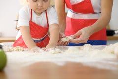 Мать и ее милые руки дочери подготавливают тесто на деревянном столе Домодельное печенье для хлеба или пиццы bakersfield стоковые фото