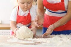 Мать и ее милые руки дочери подготавливают тесто на деревянном столе Домодельное печенье для хлеба или пиццы bakersfield стоковые фотографии rf
