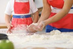 Мать и ее милые руки дочери подготавливают тесто на деревянном столе Домодельное печенье для хлеба или пиццы bakersfield стоковое изображение