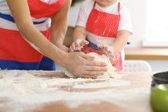 Мать и ее милые руки дочери подготавливают тесто на деревянном столе Домодельное печенье для хлеба или пиццы bakersfield стоковое фото rf