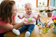 Мать и ее младенец крася пасхальные яйца Стоковое Изображение RF