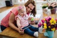 Мать и ее младенец крася пасхальные яйца Стоковые Фотографии RF
