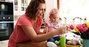 Мать и ее младенец крася пасхальные яйца Стоковая Фотография RF