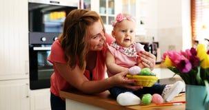 Мать и ее младенец крася пасхальные яйца Стоковое Фото
