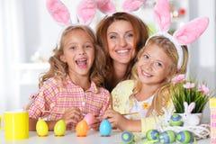 Мать и ее дочери крася пасхальные яйца Стоковое Изображение