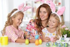 Мать и ее дочери крася пасхальные яйца Стоковые Фото