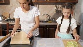 Мать и ее предназначенная для подростков дочь варят apfelstrudel яблочного пирога совместно в кухне акции видеоматериалы
