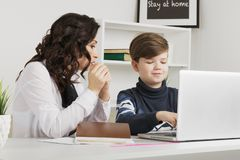 Мать и ее сын делая домашнюю работу в белой комнате Печатая домашняя работа на ноутбуке стоковые фото