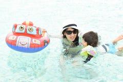 мать и ее сын играя на бассейне Стоковое Изображение