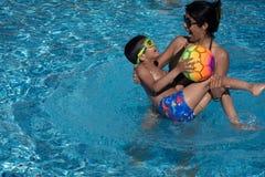 Мать и ее сын играя с шариком в бассейне на празднике стоковое изображение