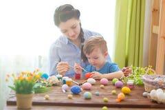Мать и ее сын крася пасхальные яйца Счастливая семья подготавливая для пасхи пасха счастливая Стоковая Фотография