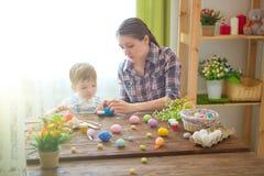 Мать и ее сын крася пасхальные яйца Счастливая семья подготавливая для пасхи пасха счастливая Стоковое Фото