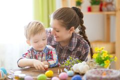 Мать и ее сын крася пасхальные яйца Счастливая семья подготавливая для пасхи пасха счастливая Стоковые Фото