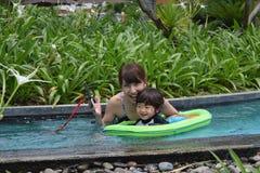 мать и ее сын palying на стороне бассейна Стоковое фото RF
