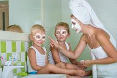 Мать и дети делают лицевой щиток гермошлема в утре Шутка мальчиков с мамой Косметики для кожи Стоковая Фотография RF