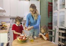 Мать и дети делая салат на кухне Стоковое Изображение