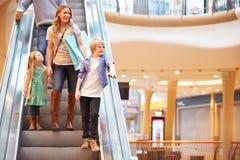 Мать и дети на эскалаторе в торговом центре Стоковые Фото