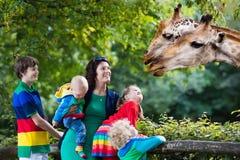 Мать и дети подавая жираф на зоопарке Стоковые Изображения