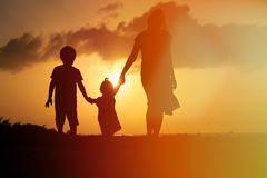 Мать и 2 дет идя на заход солнца Стоковые Фото