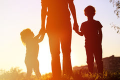 Мать и 2 дет идя на заход солнца Стоковое Изображение