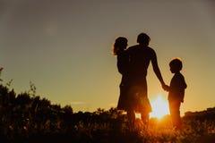 Мать и 2 дет идя на заход солнца Стоковые Изображения