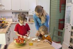 Мать и 2 дет режа сыр Стоковая Фотография