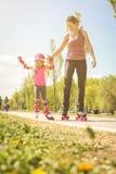 Мать и маленькая девочка в rollerblading Стоковые Фотографии RF