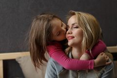 Мать и маленькая дочь играющ и обнимающ на кровати счастливое материнство стоковое изображение