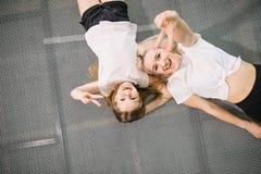 Мать и маленькая дочь играя на спортивной площадке и лежа на батуте стоковые фото